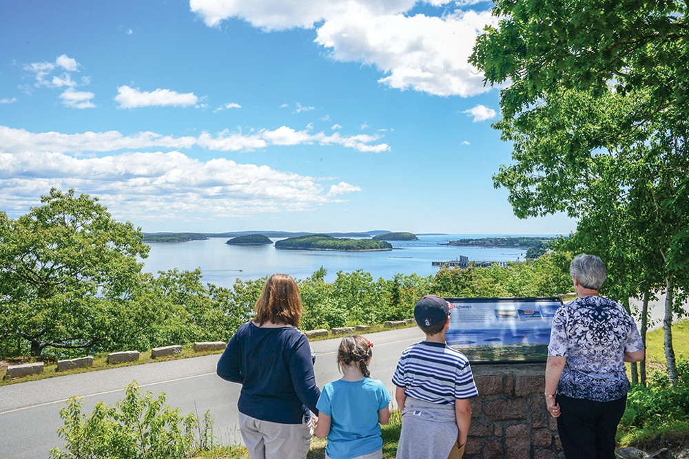 Visitors scan a key to the islands in Frenchman Bay at a stop along the Park Loop Road, which connects Acadia's lakes, forests, mountains and shores.
