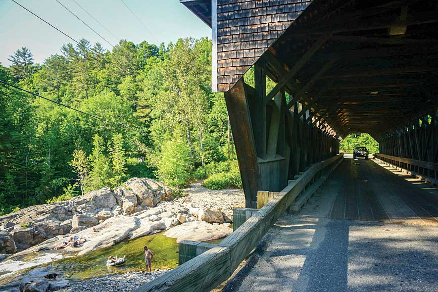 In the town of Bath, a car crosses the 158-foot-long Swiftwater Bridge, built in 1849, as bathers sun themselves on the rocks of the Wild Ammonoosuc River below the historic span.
