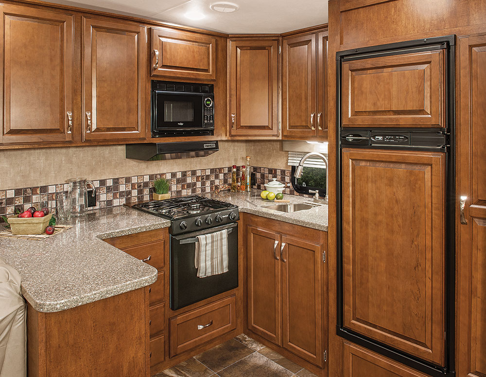 The rear kitchen complex puts all of the galley amenities within  easy reach of the cook. Solid-surface countertops and surrounding cabinets and drawers make it simple to organize the kitchen and comfortable to access the storage areas.