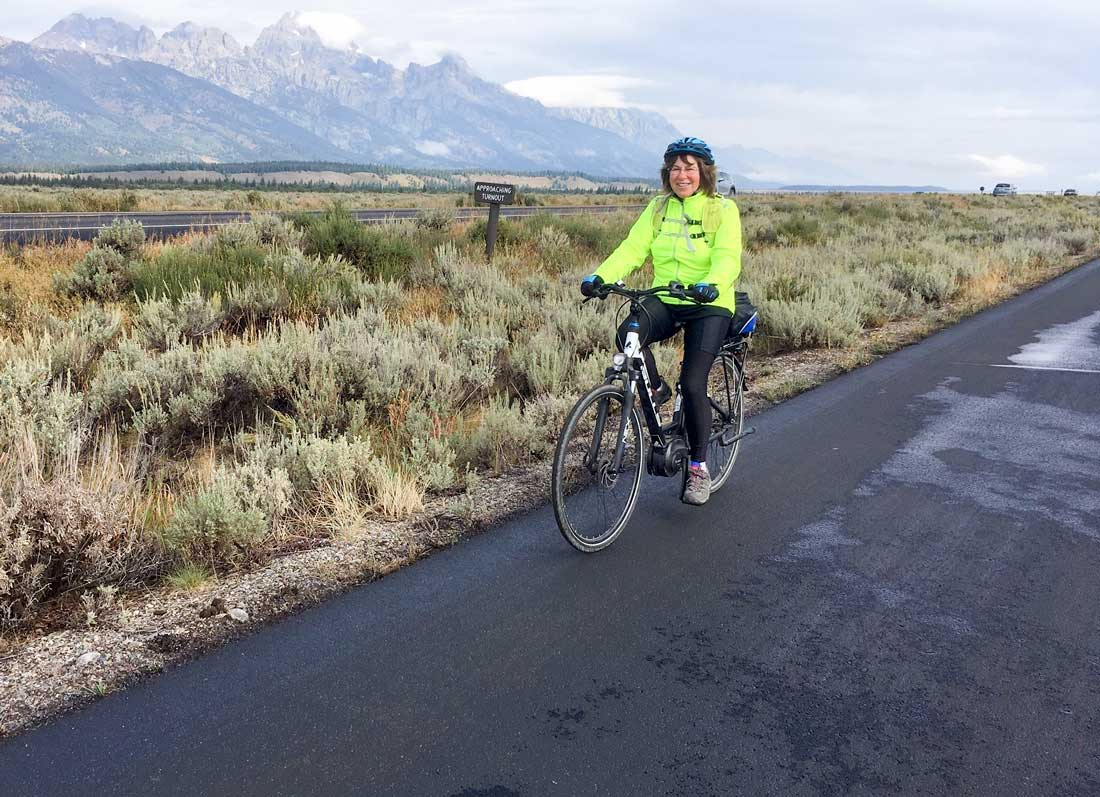 Author Ruth Edelman enjoys a ride on her e-bike with the Teton Mountains in the background.