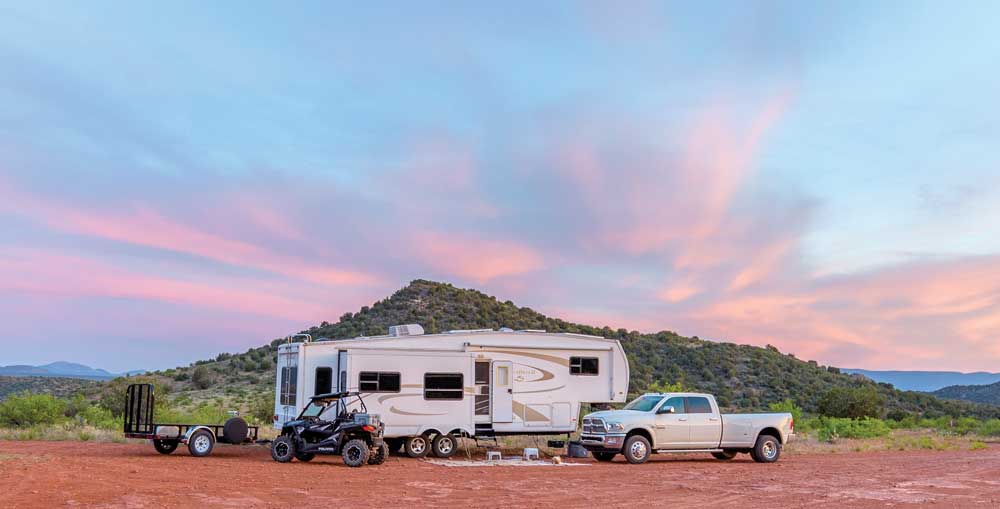 The Fagan's fifth-wheel trailer, truck, Razor side by side and utility trailer are parked under a sunset sky