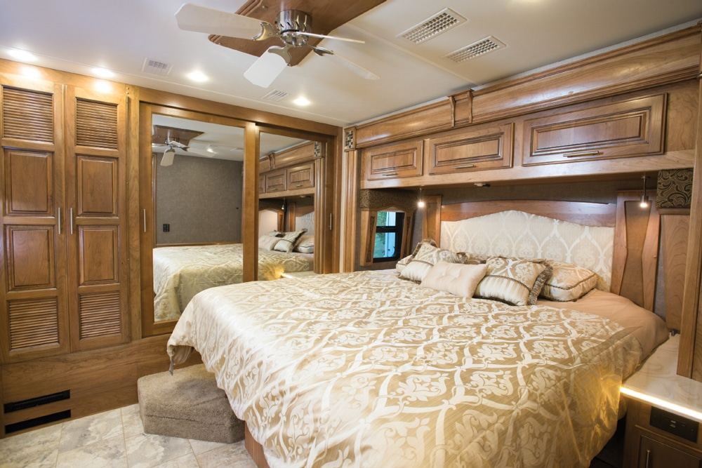 The king bed is housed in a streetside slideout in the master. Handy solid surfaces on each side are perfect for nightstand duties. A large closet runs the length of the back wall.