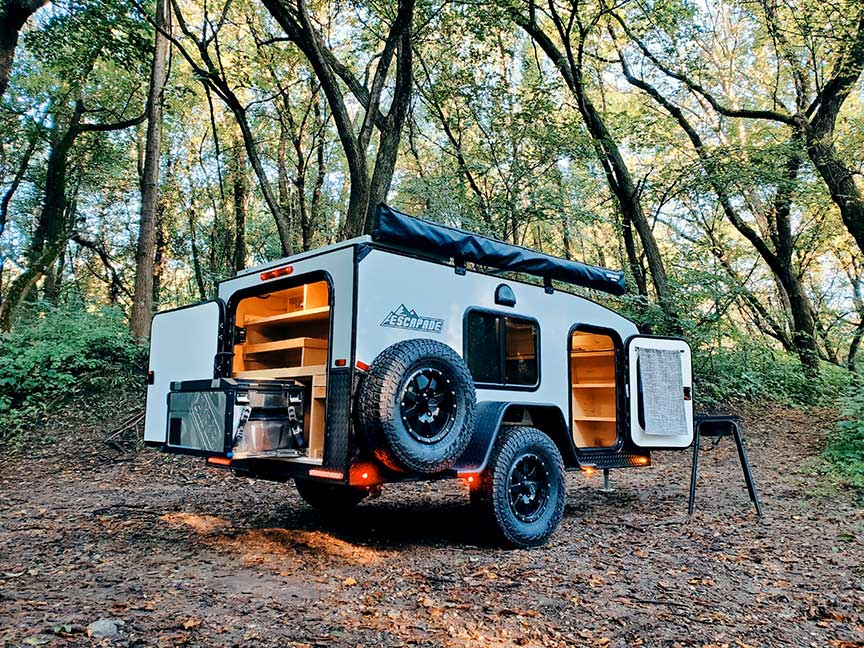 Silver Escapade trailer with doors open at dusk.