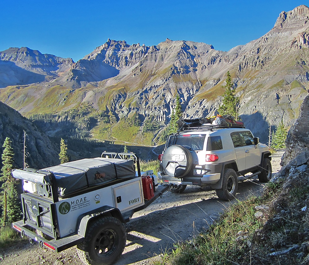 Silver SUV with camping gear attached on top towing 2-wheel MOAB travel trailer in mountains
