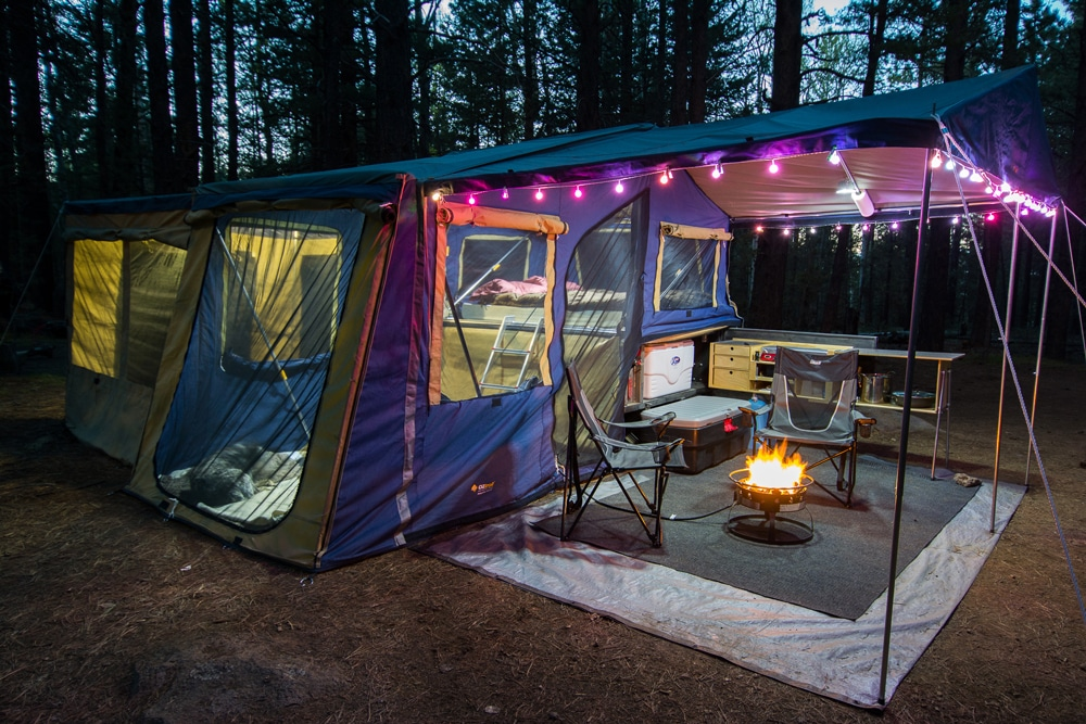 Colorful tent with awning lit up with purple lights and fire pit in woods