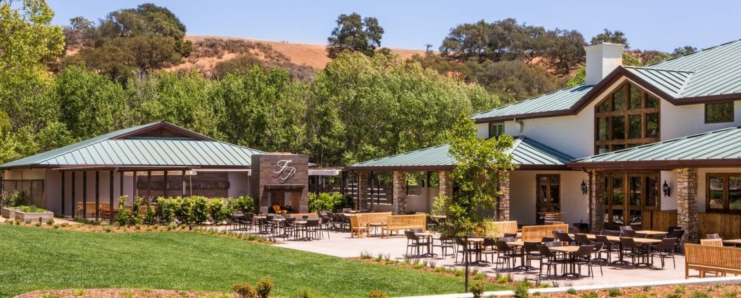 Large wooden winery buildings with patio area amidst green trees