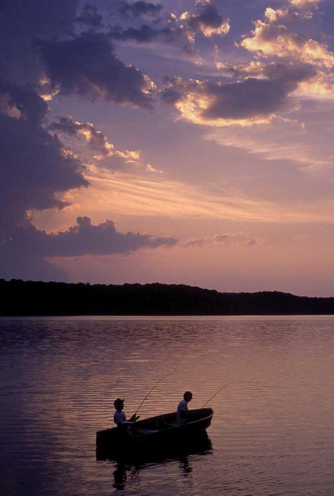Fishermen in boat on lake at sunset