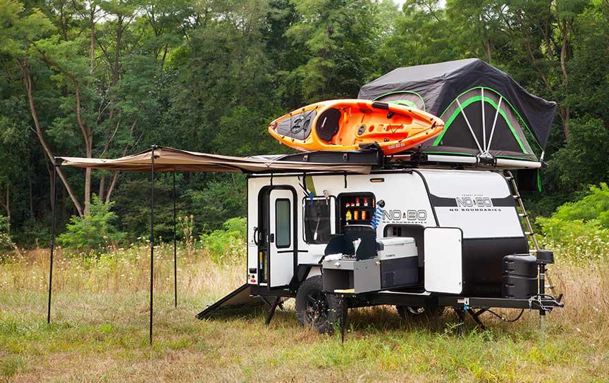 No Boundaries trailer with orange kayak and rooftop tent.