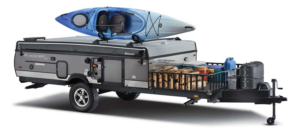 Kayak on the cargo rack of a folding camping trailer with gear in the cargo basket