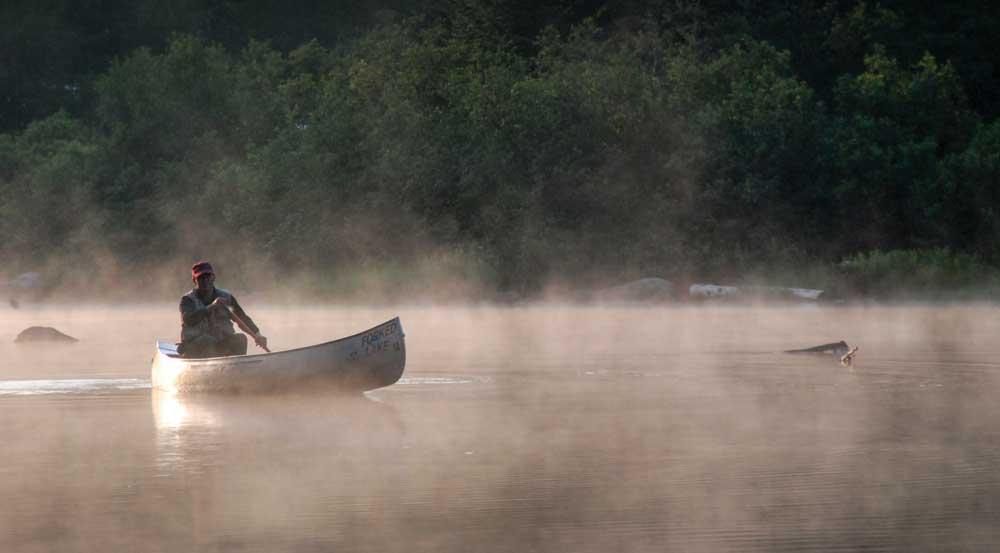 Single canoer on lake shrouded in mist