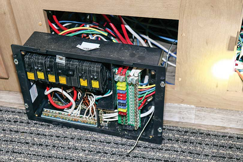 Photo shows the circuit breaker/fuse box pulled out from its mounting so the wires can be routed through the back of it.