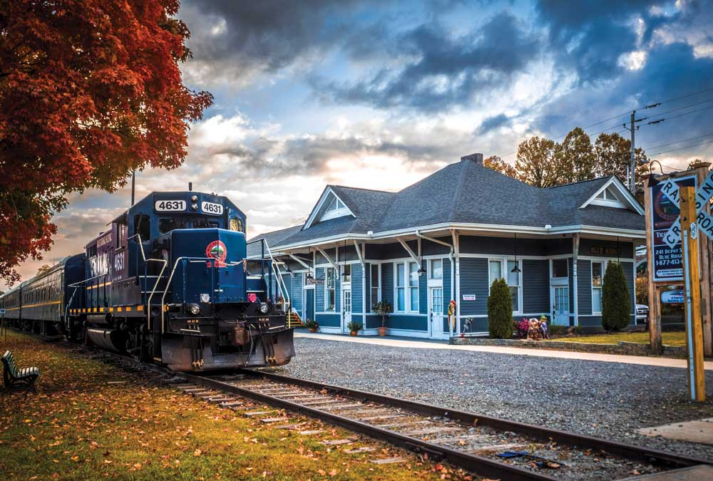A Blue Ridge Scenic Railway locomotive sits in the station beneath fall leaves and a dark cloudy sky.