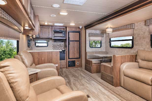 The 34½-foot rear-kitchen GEO 293RK has two recliners and a dinette and jackknife sofa are housed in a slide. Titanium decor (shown) in a soft-touch vinyl is paired with a print fabric.