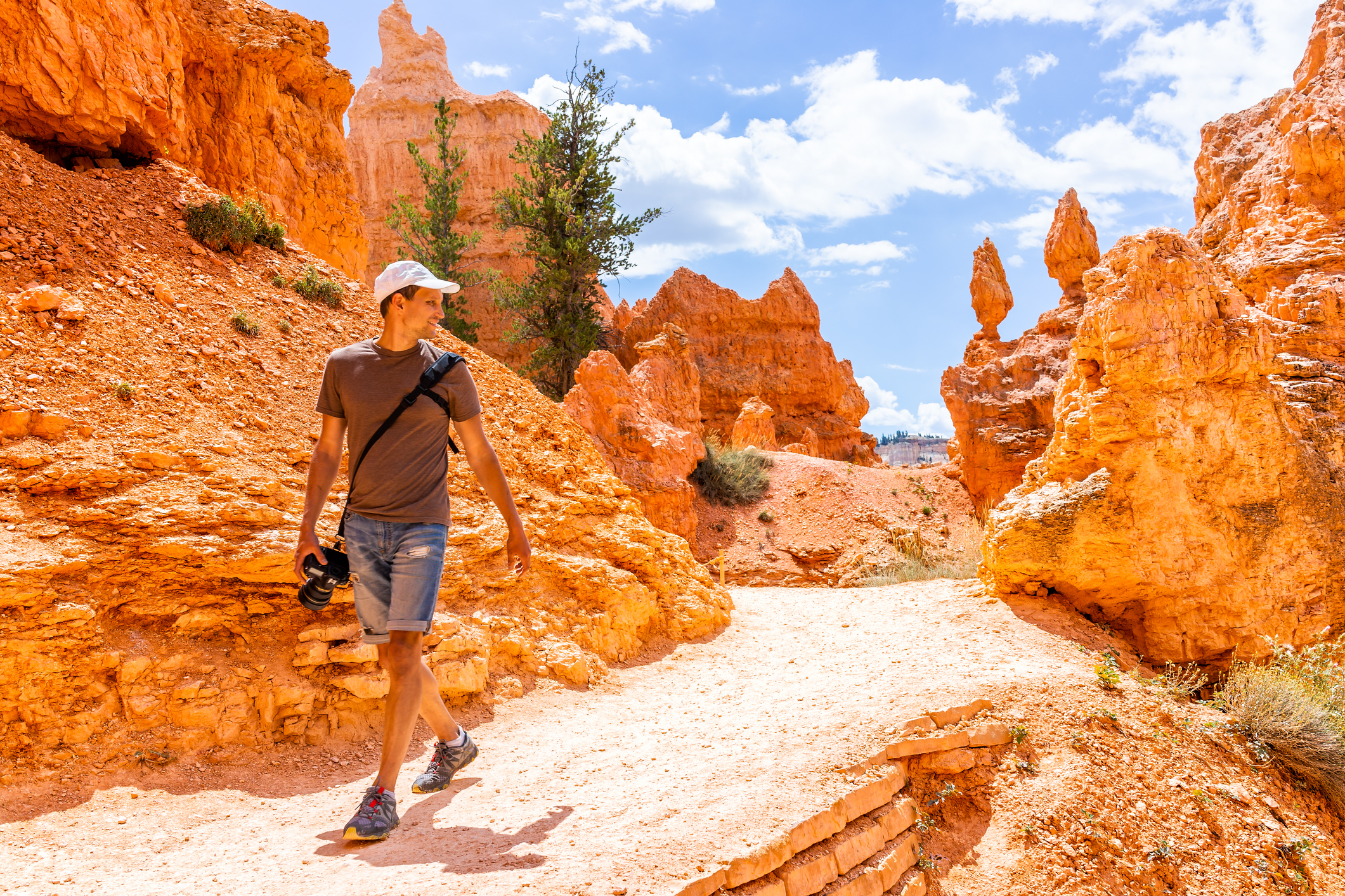 Man tourist person walking motion by orange color formations at Queens Garden Navajo Loop trail at Bryce Canyon National Park in Utah with camera