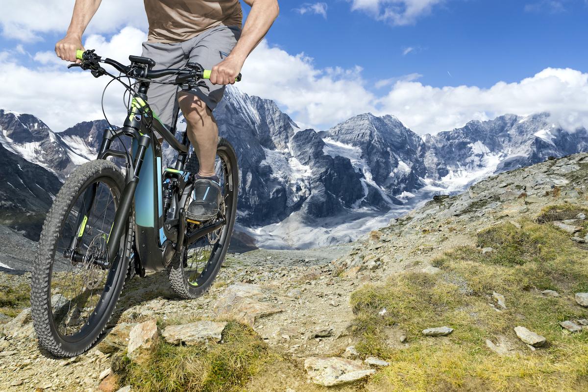 Single mountain bike rider on E bike rides up a steep mountain trail.