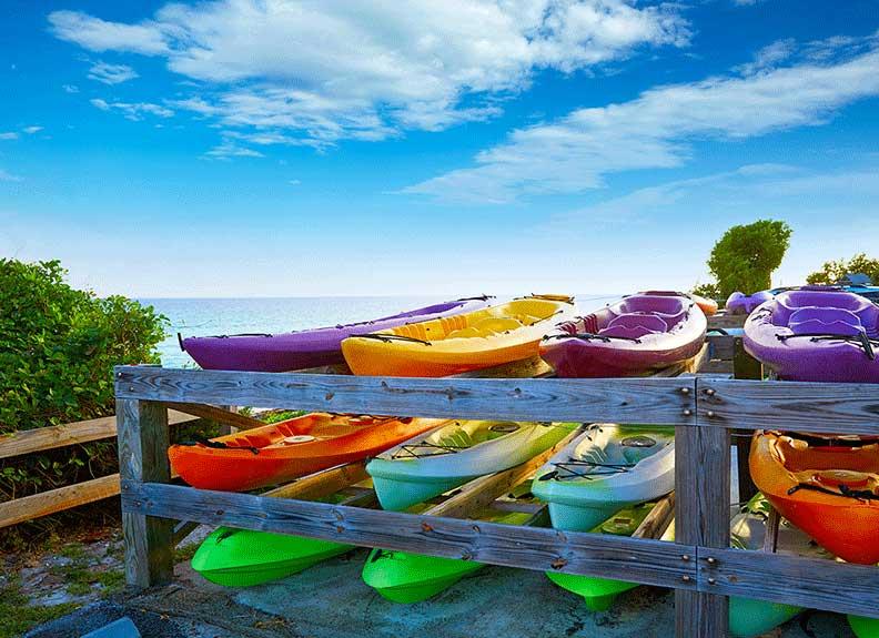 Nine colorful kayaks on a rack at the beach.