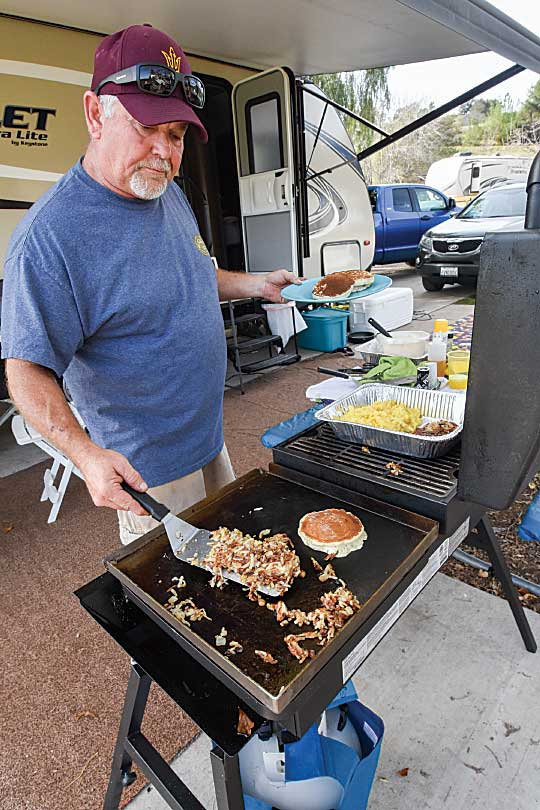Cooking a traditional campsite breakfast on an outdoor grill on an RV patio