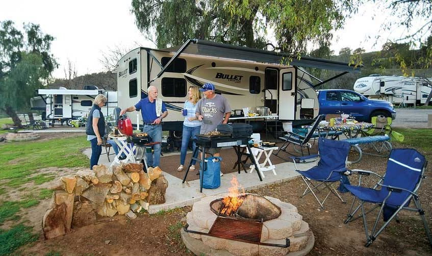 Four people cooking on grills in front of travel trailer