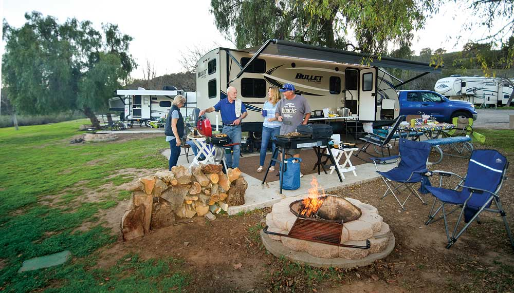 Couples grilling on the RV patio with campfire and campground in the background
