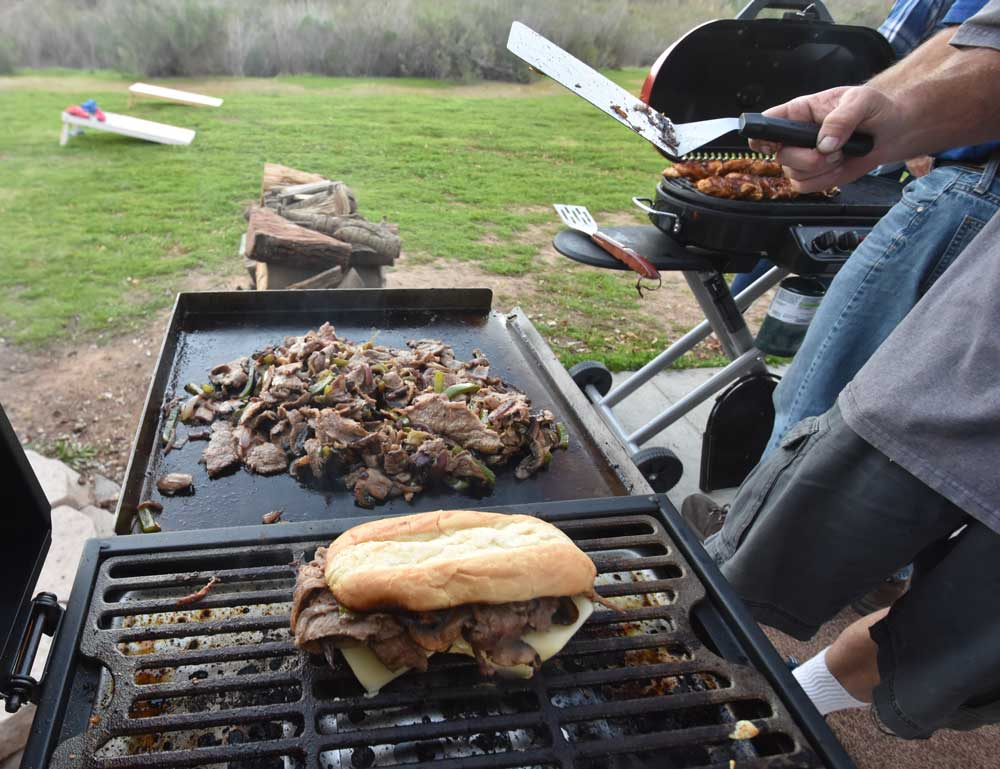 A philly cheese steak sandwich warms on the blackstone tailgater grill while more ingredients are cooked on the griddle side of the grill