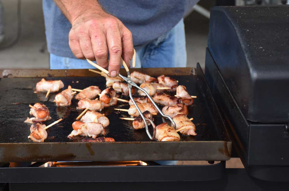 Preparing bacon wrapped shrimp and smokies on an outdoor grill