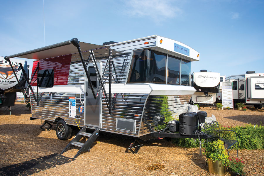 Silver and white striped travel trailer with awning out