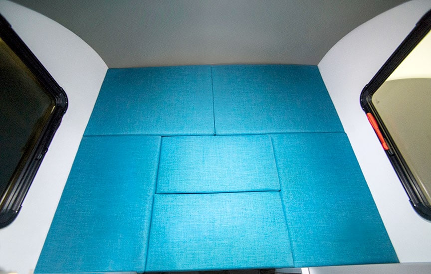 Trailer bed made up with turquoise cushions.