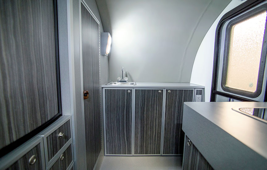 Sink and counter area of trailer with enclosed shower door closed.