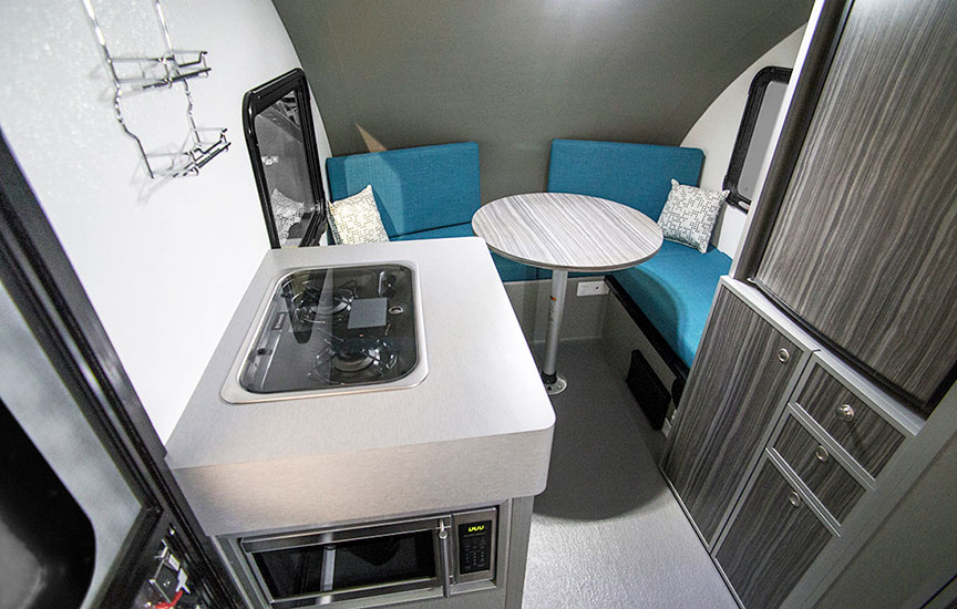 Inside trailer showing the cooktop, table and bench seats.