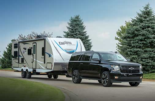 a travel trailer hitched up to a Chevy SUV