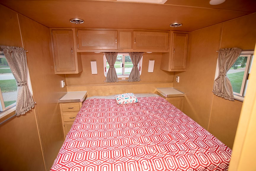 Walk-around queen bed with red and white bedspread and paneled walls in Holiday House trailer