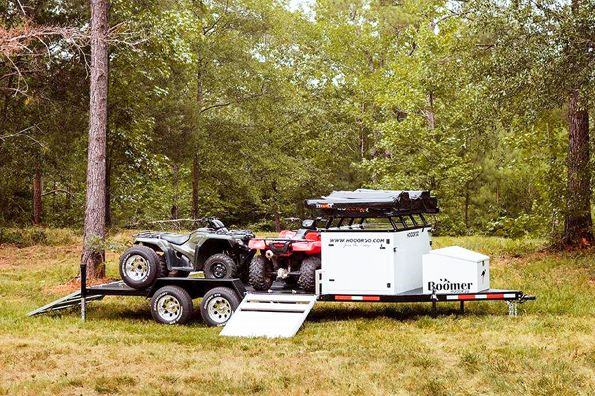 Boomer trailer on grass with two ATVs.