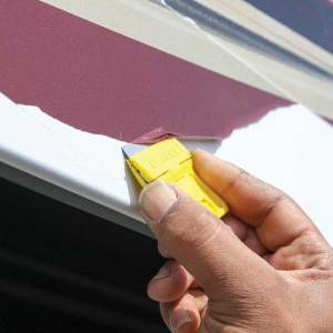 A razor blade is used to remove the old graphics.