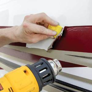 A heat gun softens the vinyl to make it possible to remove the old material.