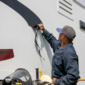 Darker-color vinyl is easier to remove than lighter counterparts. Here, the installer can remove big sections of vinyl by hand, even though it's the same age as the rest of the original material.