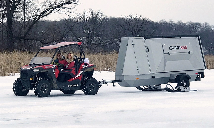 An off-road vehicle pulling the trailer on ice in winter.