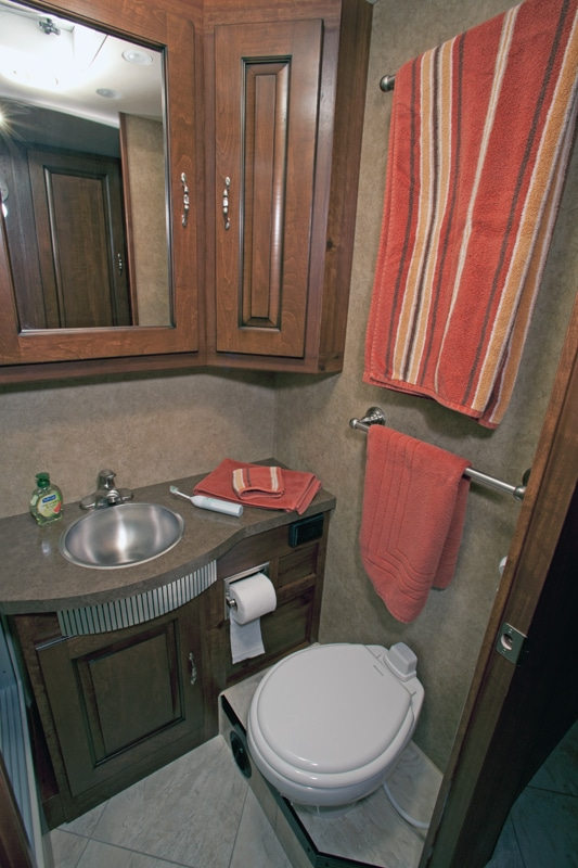 The well-appointed lav has a porcelain toilet with 16 inches of foot space.