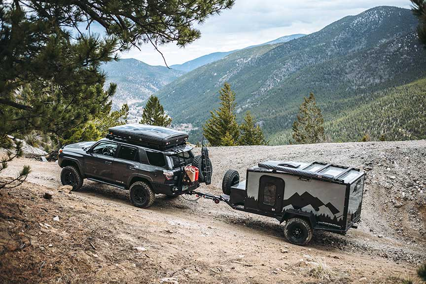 Into the Wild Overland trailer towed off road up a mountain.