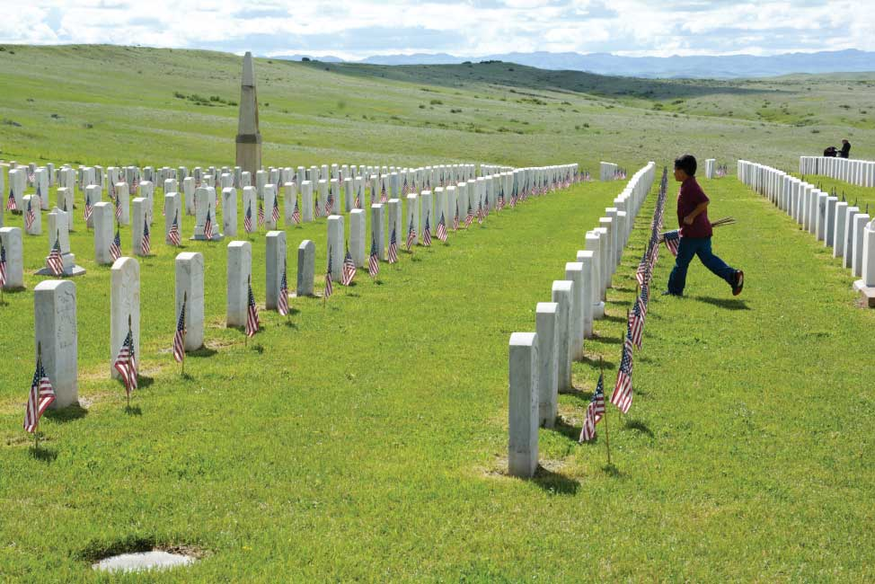 A student from one of the St. Labre Indian Schools decorates headstones just before Memorial Day at the nationally known Little Bighorn Battlefield.