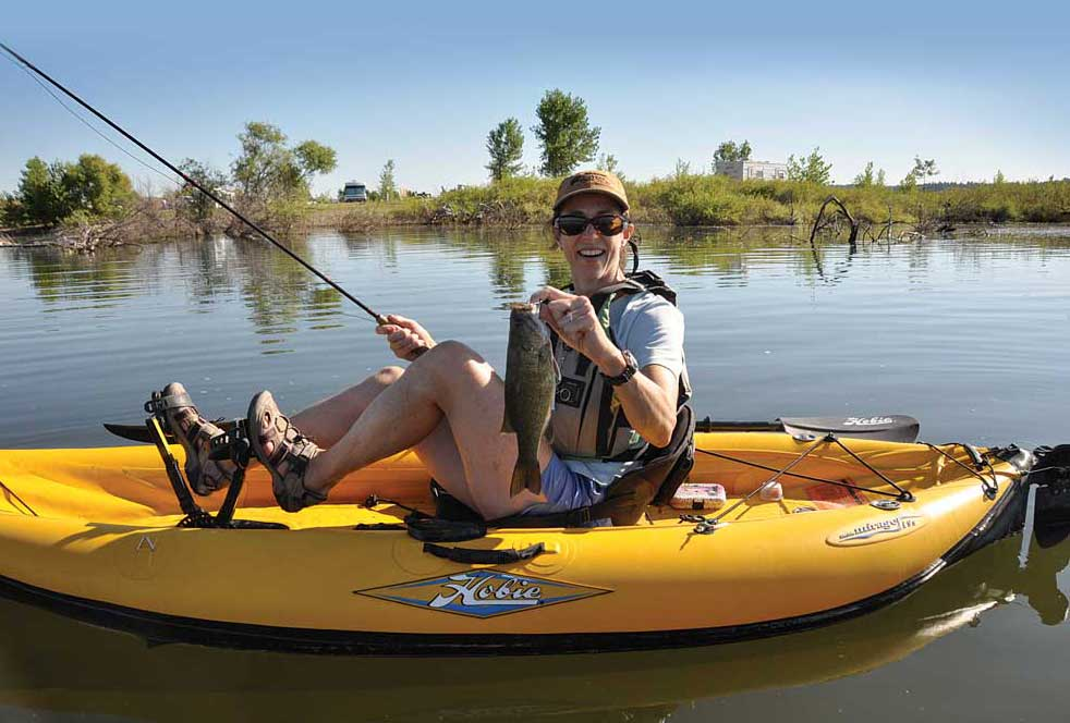 An angler on a kayak shows off a recently caught smallmaout bass