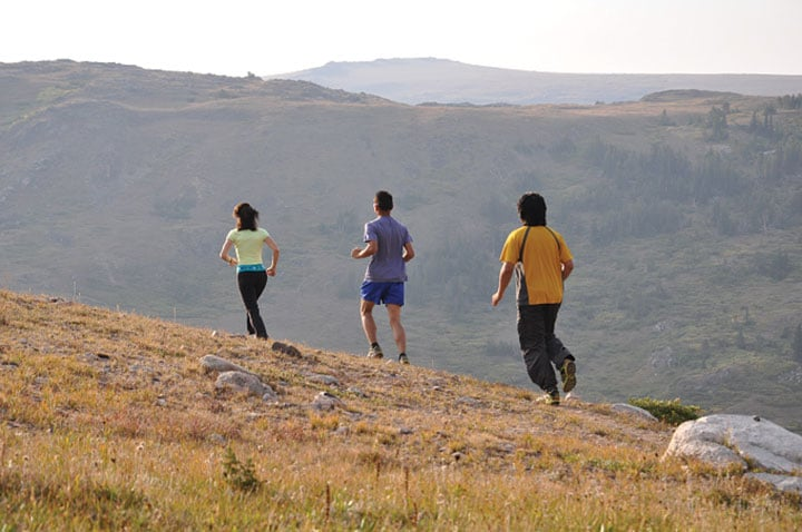 Three people running on trail to stay fit