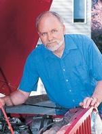 Older man wearing blue shit standing over open vehicle hood