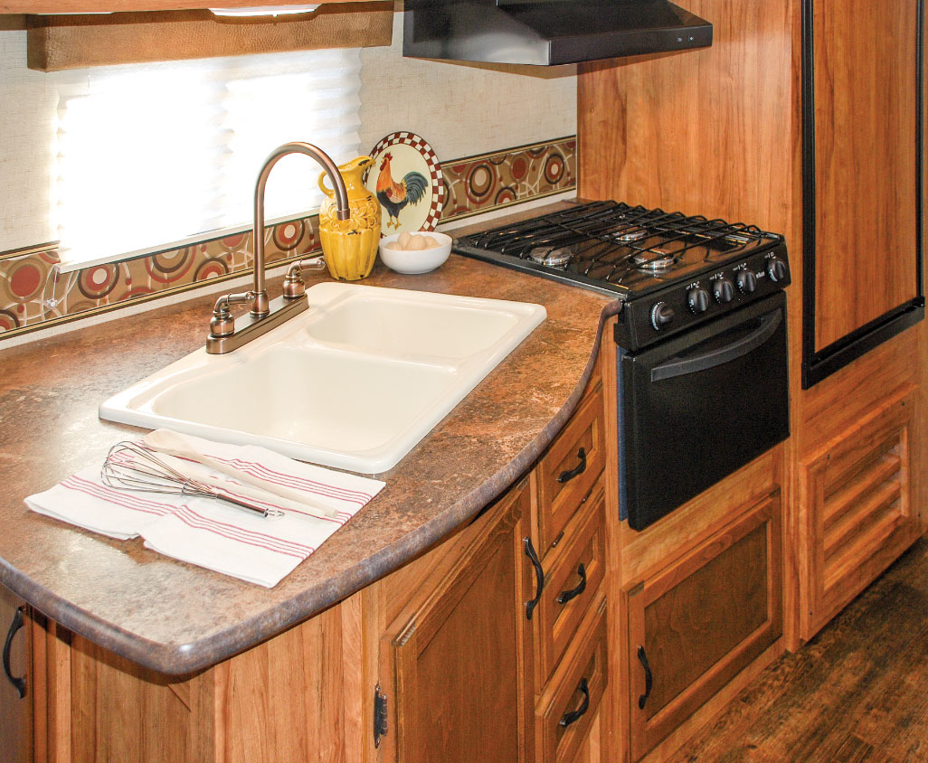 Maple cabinetry, a decorative border and a high-rise faucet perk up the galley.