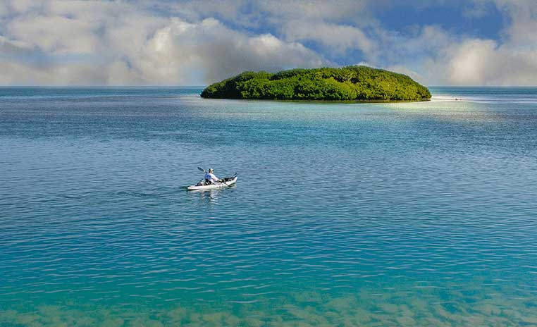 A lone kayaker paddling toward a small island