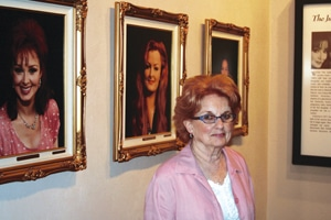 Older red headed woman with glasses standing near framed pictures of other women