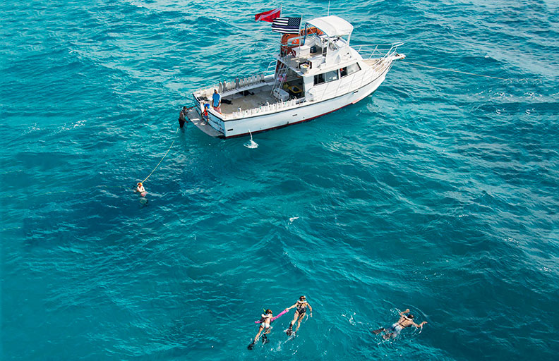 A dive boat on the water surrounded by several snorkelers.