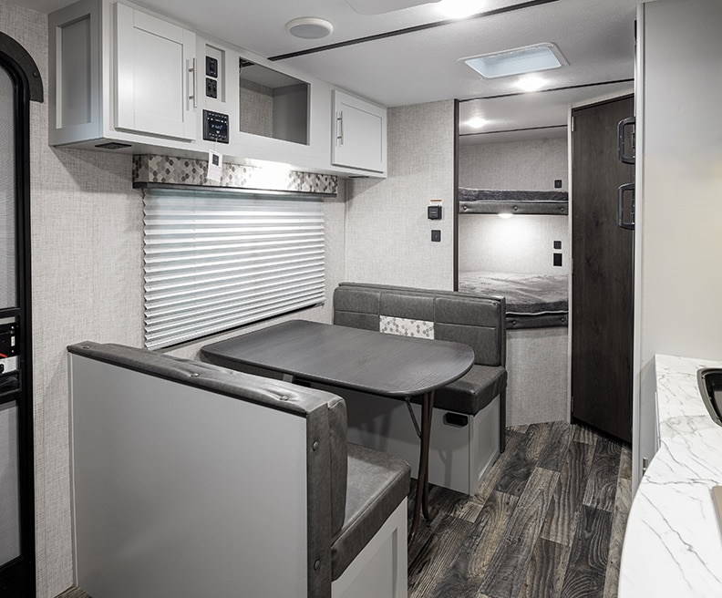 White interior with gray bench dinette and white cabinets above it. Bunks in the rear.