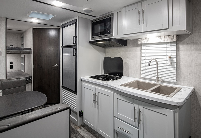 White cabinets in the kitchen with stainless refrigerator and microwave.