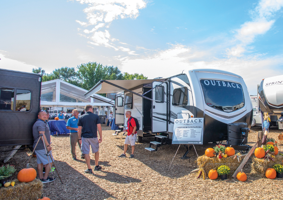 Outback travel trailer parked with people standing and pumpkins on ground