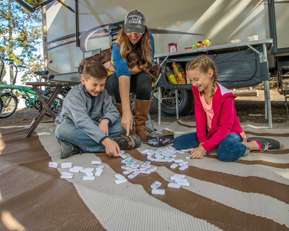Family camping playing dominoes